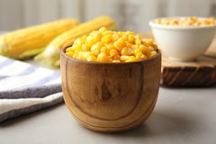 Bowl with corn kernels. On grey table Royalty Free Stock Photos