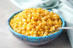 Bowl with corn kernels. On grey table Stock Image
