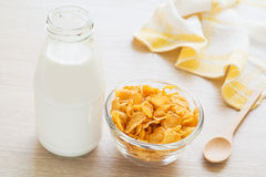 Bowl of cornflake and milk bottle on table Stock Image