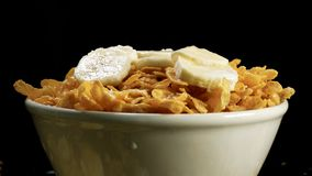 Cereal, banana and milk in a bowl stock footage