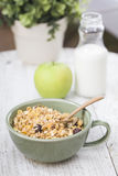 A bowl of cornflakes, an apple and a bottle of milk on a wood table. A bowl of cornflakes, a green apple and a bottle of milk on a wood table Stock Photos