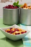 Bowl with cornflakes in front of two aluminum cups Royalty Free Stock Photos