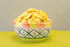 Bowl with cornflakes on the green textured background royalty free stock photos