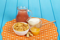 Bowl cornflakes, jug juice, yogurt, honey and peanuts on blue. Stock Photo