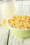 Bowl of cornflakes with milk on white wooden background Royalty Free Stock Photo