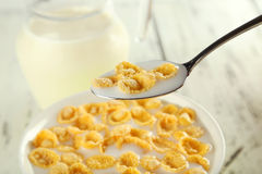 Bowl of cornflakes with milk on white wooden background. Royalty Free Stock Photo