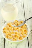 Bowl of cornflakes with milk on white wooden background. Royalty Free Stock Photography