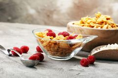 Bowl of Cornflakes and Raspberries for a healthy breakfast conce. Pt on rustic grey background Royalty Free Stock Photos