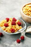 Bowl of Cornflakes and Raspberries for a healthy breakfast conce. Pt on rustic grey background Royalty Free Stock Images
