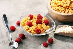 Bowl of Cornflakes and Raspberries for a healthy breakfast conce. Pt on rustic grey background Stock Images