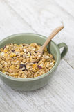 A bowl of cornflakes on a wood table. A bowl of cornflakes on a white wood table Royalty Free Stock Photography