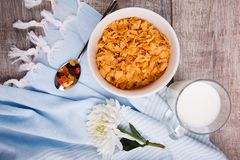 In a bowl of cornflakes a wooden background, next is a glass of milk, next to a white flower, top view royalty free stock photo