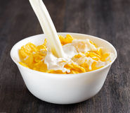 Bowl of cornflakes on wooden table Stock Images