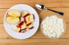 Bowl with cottage cheese and plate with pieces of apple Royalty Free Stock Photos