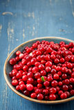 Bowl of cowberries. On blue wooden table Royalty Free Stock Photography