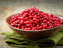 Bowl of cowberries. On old wooden table Stock Photos