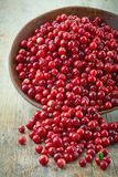 Bowl of cowberries. On old wooden table Royalty Free Stock Photography