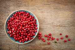 Bowl of cowberries. On old wooden table Royalty Free Stock Photos