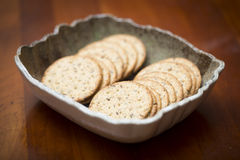 Bowl of crackers. A bowl full of delicious wheat crackers on a cherry wood table Royalty Free Stock Images