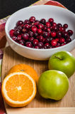 Bowl of cranberries with apples and oranges on board Stock Photography