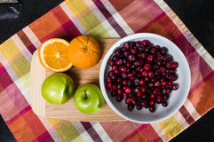 Bowl of cranberries with apples and oranges Stock Photos
