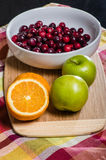 Bowl of cranberries with apples and oranges Royalty Free Stock Images