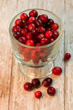 Bowl of Cranberries on a wooden background. A bowl of whole cranberries on a white wooden background stock photos