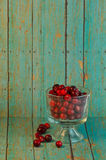 Bowl of Cranberries on a wooden turquoise background. A bowl of red cranberries on a blueish green wooden plank background stock image