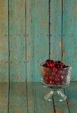Bowl of Cranberries on a wooden turquoise background. A bowl of red cranberries on a blueish green wooden plank background stock images