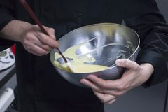 Bowl with cream being stirred on a chef´s hands. Bowl with cream being stirred by a chef wearing black suit with his moving hands. Kitchen pastry actions on Stock Photo