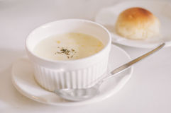 A bowl of cream soup with bun. On white dishes and table Stock Images