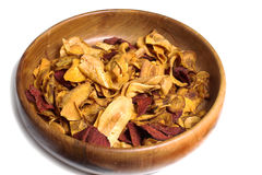 Bowl of crisps. Carved wooden bowl with crisps made from various root vegetables Stock Photo