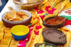 Bowl of crunchy delicous tortilla chips sitting on native american table cloth, next to different salsas.  Stock Photos