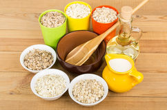Bowl and cups with oat, rye, barley flakes, vegetable oil Royalty Free Stock Photography