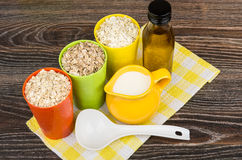 Bowl and cups with oat, rye, barley flakes, vegetable oil Stock Photos