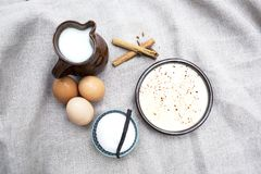 Bowl with custard and ingredients to make it. Bowl with custard sprinkled with powdered cinnamon and ingredients to make it such as jug of milk, cinnamon sticks Stock Image