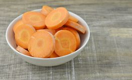 The food good for eyes on white bowl, fresh carrots. Bowl with cut carrots thin on wooden background royalty free stock photos
