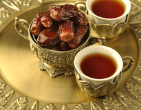 Bowl of dates and tea. A vintage bowl of dates and a tea cup in a tray Stock Photo