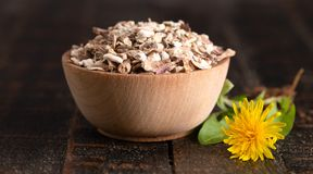 Bowl of Dehydrated Dandelion Root on a Rustic Wooden Table. A Bowl of Dehydrated Dandelion Root on a Rustic Wooden Table royalty free stock photos