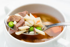 A bowl of delicious beef and barley soup with carrots, tomato, potato, celery, and peas. Royalty Free Stock Image