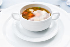 A bowl of delicious beef and barley soup with carrots, tomato, potato, celery, and peas. Stock Image
