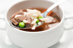 A bowl of delicious beef and barley soup with carrots, tomato, potato, celery, and peas. Royalty Free Stock Images