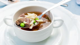 A bowl of delicious beef and barley soup with carrots, tomato, potato, celery, and peas. stock footage