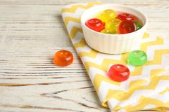 Bowl with delicious colorful candies on wooden table. Space for text royalty free stock photography