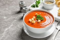 Bowl with delicious fresh homemade tomato soup on table. Space for text royalty free stock photo