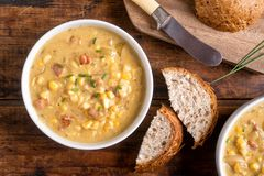 Bacon Corn Chowder. A bowl of delicious homemade bacon corn chowder with whole grain bread on a rustic wood table top stock image