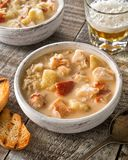 Creamy Lobster Chowder. A bowl of delicious homemade lobster chowder with grilled bread and beer royalty free stock image