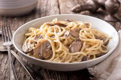 Pasta Alfredo with Mushrooms. A bowl of delicious pasta alfredo with mushrooms on a rustic table top stock photography