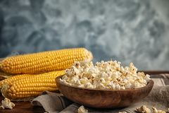 Bowl with delicious popcorn and cobs. On table Stock Photos