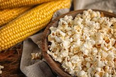 Bowl with delicious popcorn and cobs on table. Closeup Royalty Free Stock Image